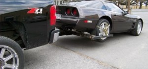 A regular pickup towing a car using an automatic lift system