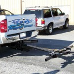 An automatic wheel lift attached to a pickup truck for towing cars.