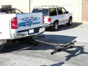 A wheel lift attached to a pickup truck to tow cars.