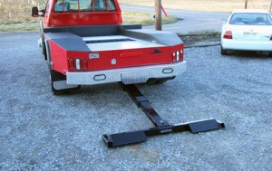Pickup truck with a lift and tow hidden wheel lift attached and deployed.