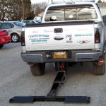 Truck with a hidden wheel lift system deployed for towing use.